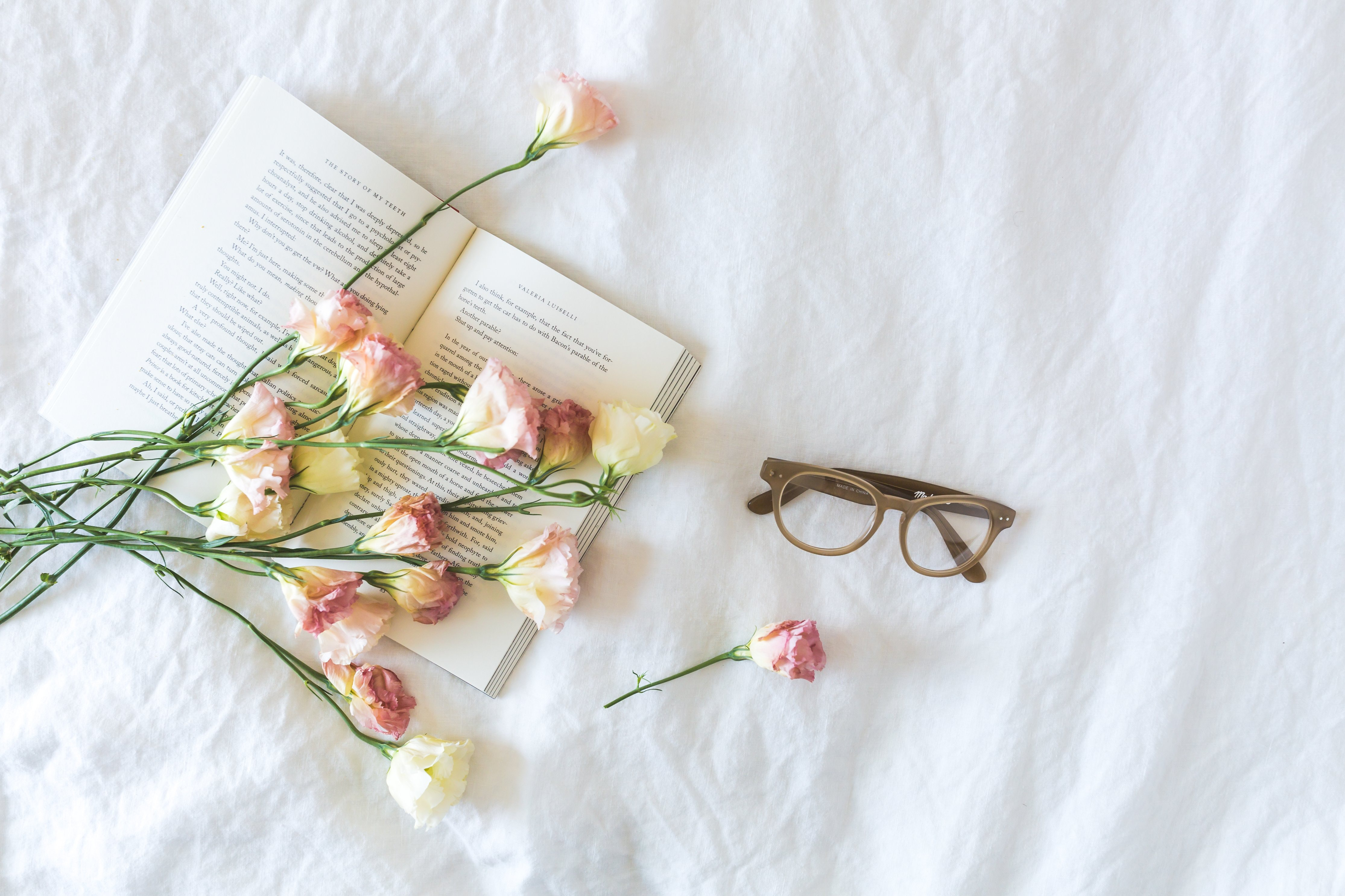 white-and-pink-flowerson-a-book-beside-eyeglasses-545042