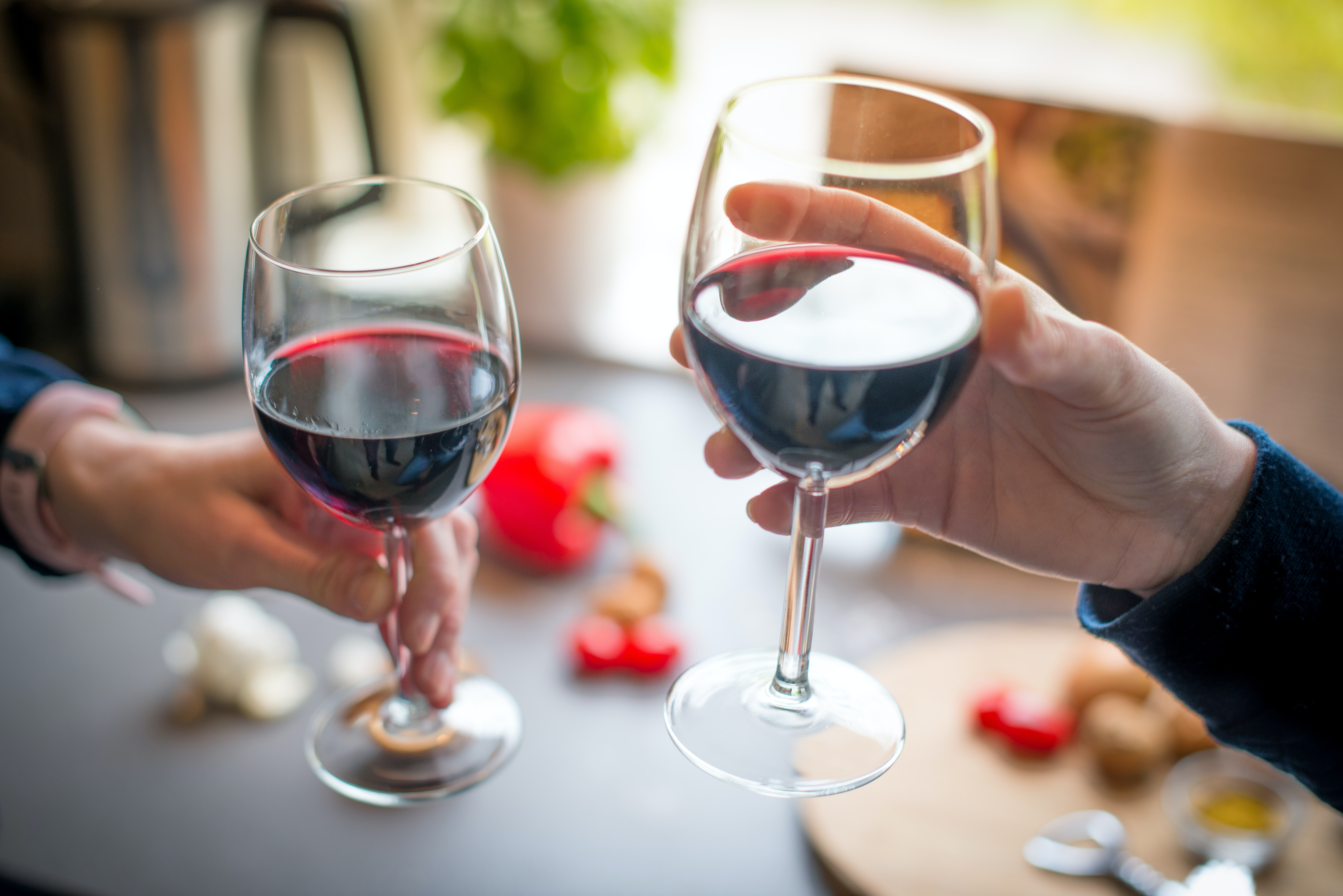 close-up-photo-of-two-people-toasting-with-red-wine-2101186