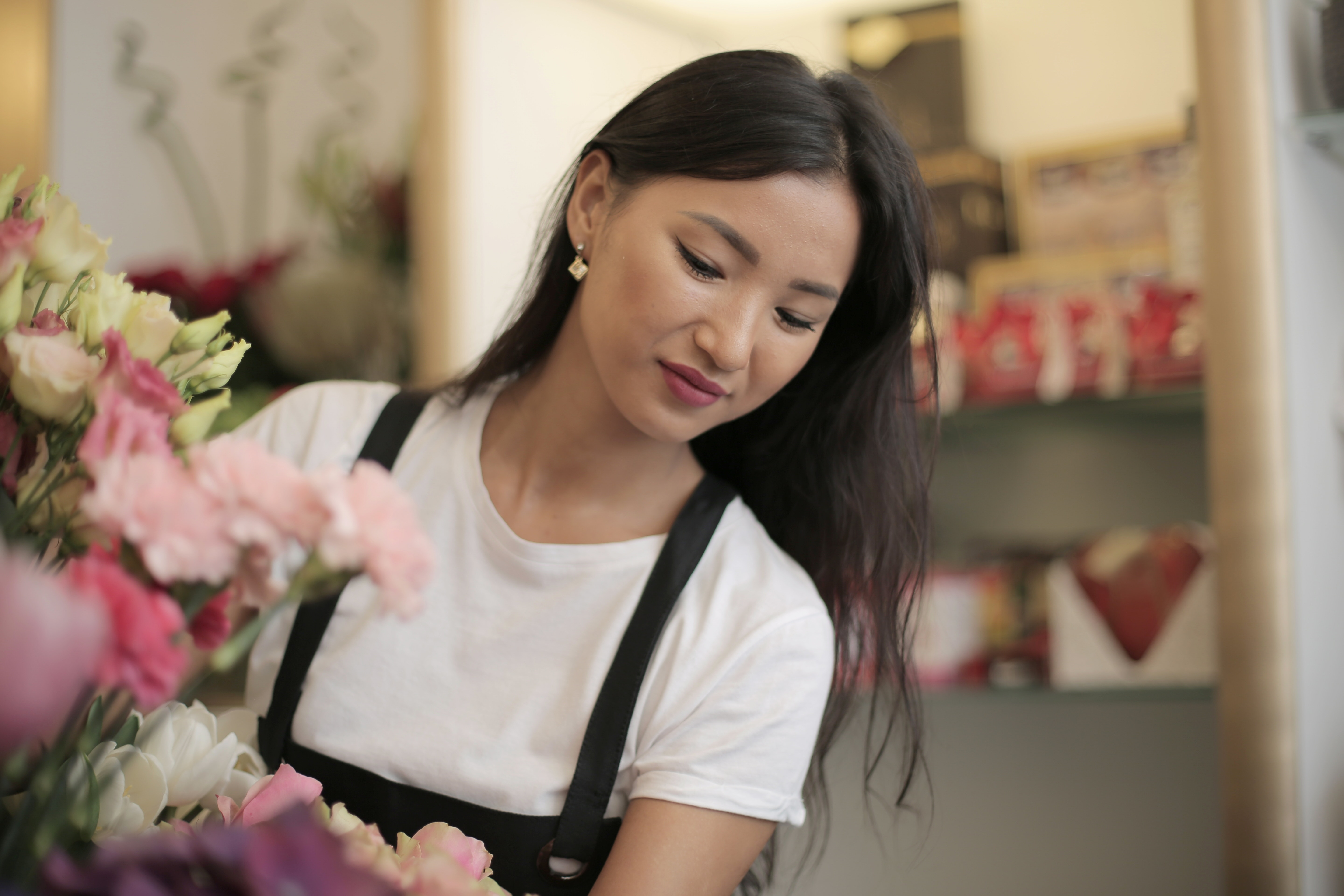happy-woman-in-uniform-with-flowers-in-shop-3933005