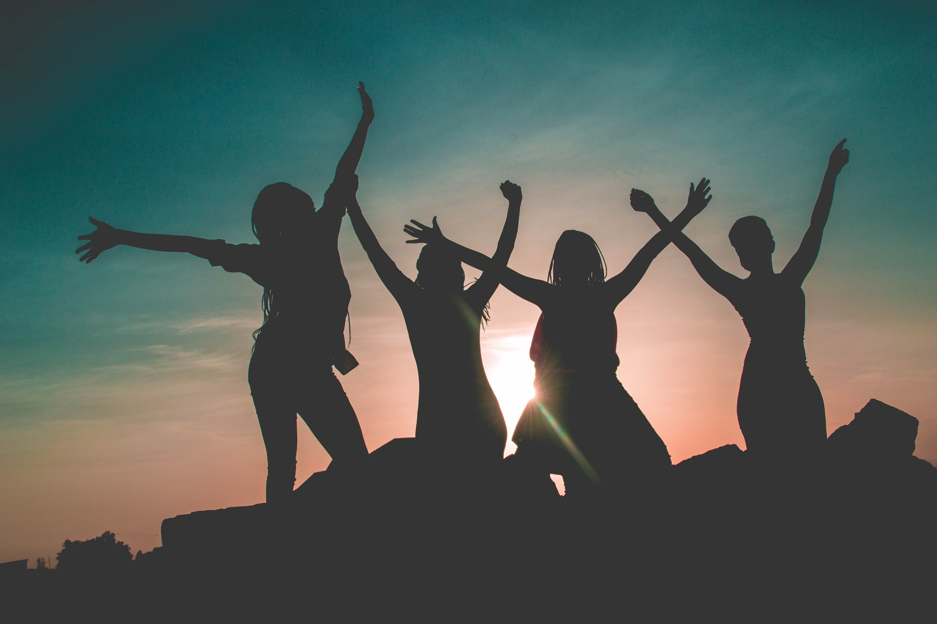 silhouette-of-four-people-against-sun-background-862848
