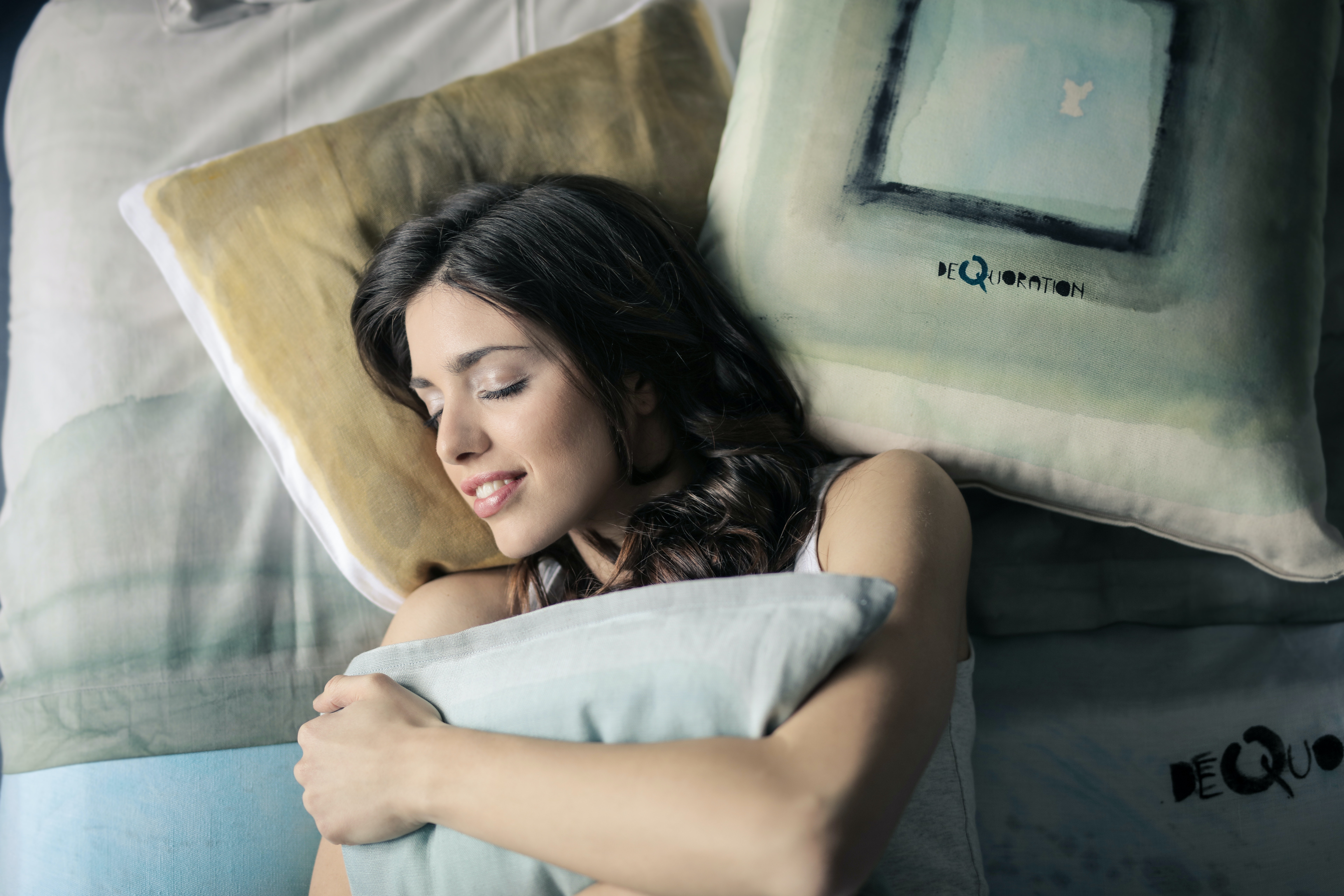 woman-wearing-white-tank-top-sleeping-on-gray-and-white-920380