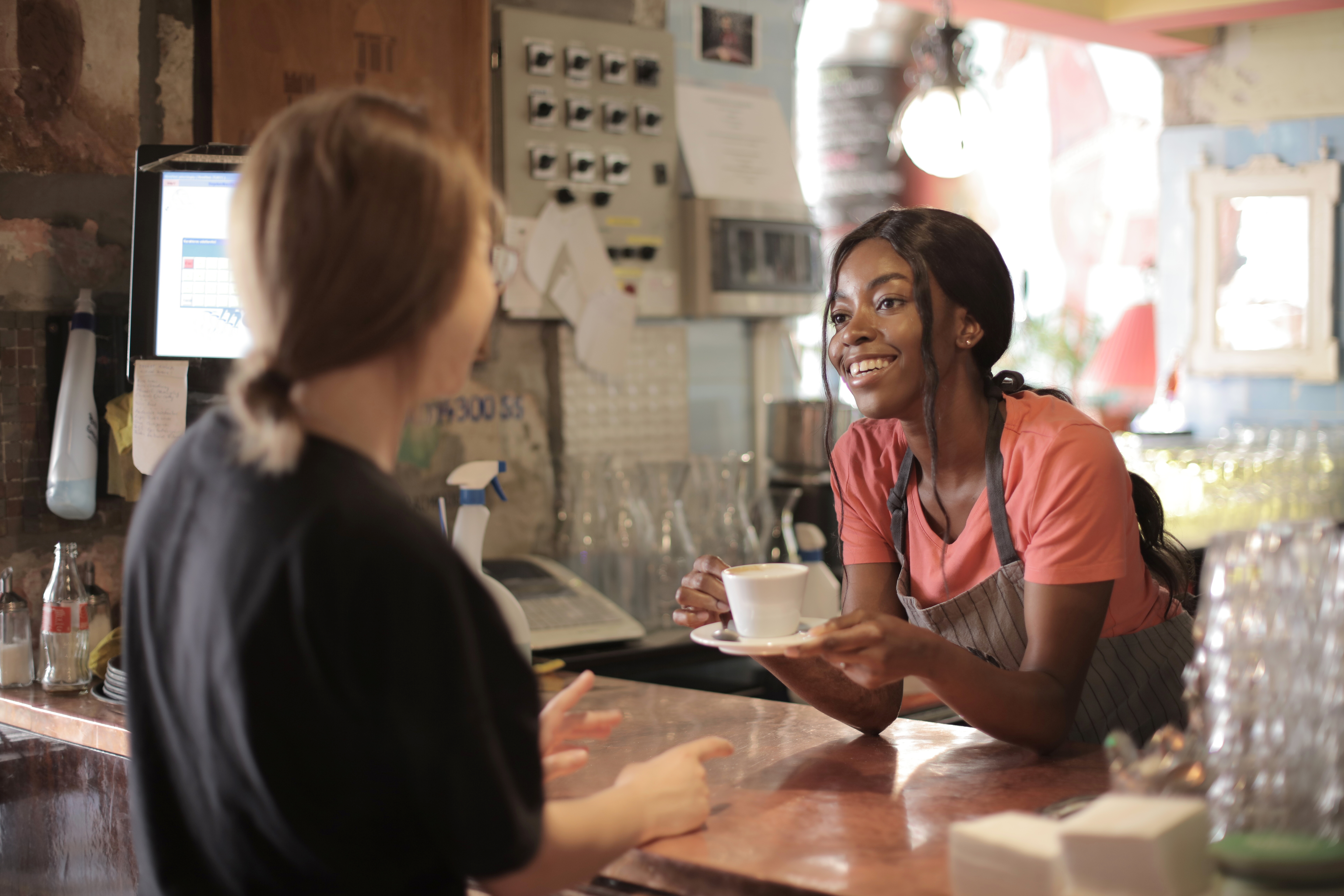 delighted-black-female-barista-serving-coffee-in-cup-in-cafe-3796810
